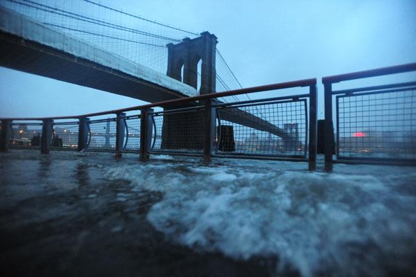 The East River crests the promenade between the Manhattan and Brooklyn Bridges. (Photo: ZUMA Press)