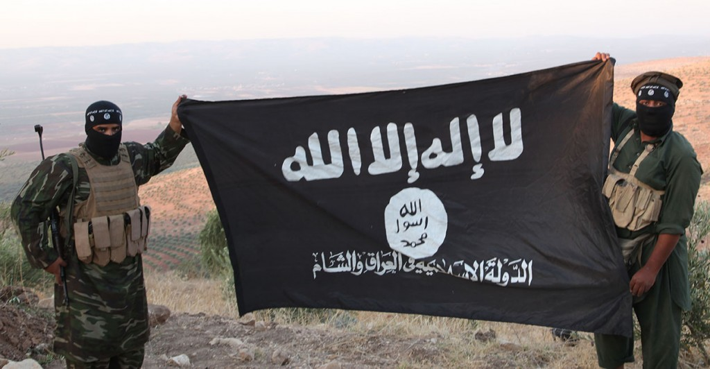 ISIS fighters holding the Al-Qaeda flag with Islamic State of Iraq and the Levant written on it. (Photo: Medyan Dairieh/Newscom)