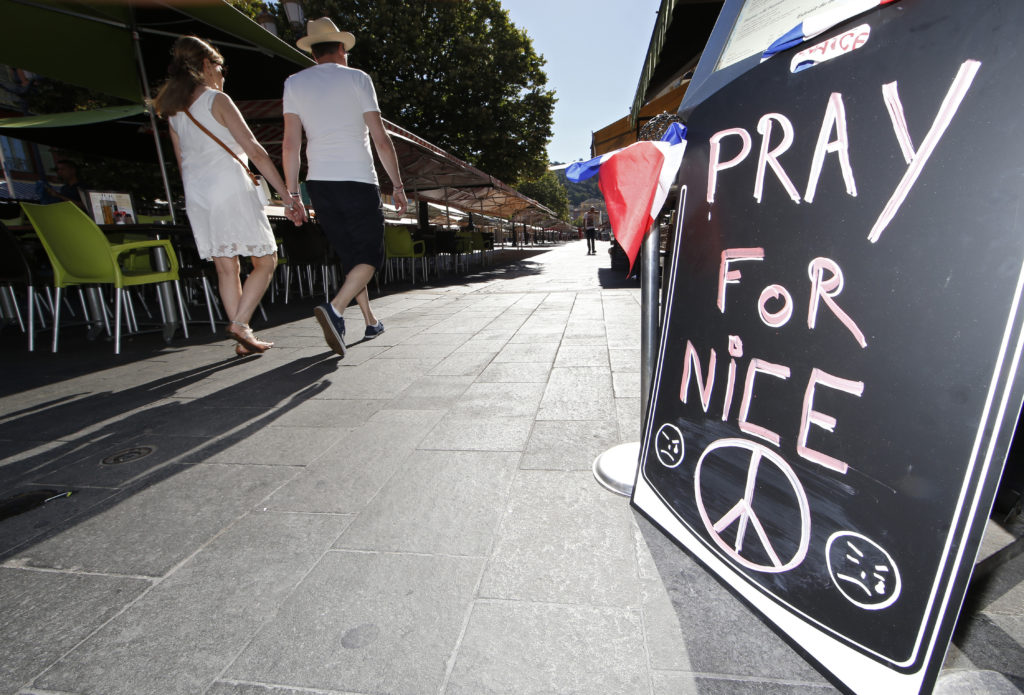 A couple walk through the empty flower market in the old city and near a sign which reads, Pray for Nice days after a truck attack on the Promenade des Anglais on Bastille Day killed scores and injured as many in Nice, France, July 17. (Photo: ERIC GAILLARD/REUTERS/Newscom)