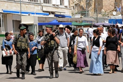 Israeli border police guard a group of Israeli tourists visiting Hebron in April 2014.