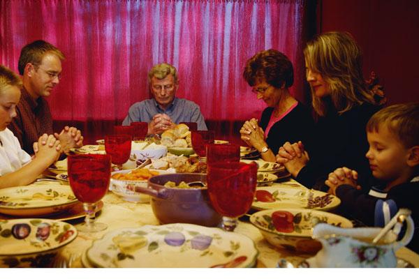 Family praying at Thanksgiving dinner