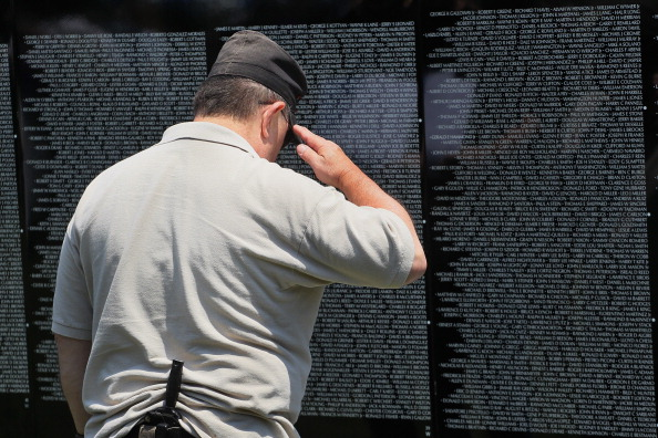 Dennis Lovick, who served in Vietnam with the Army from 1967 to 1969, salutes the name of a fallen friend inscribed on the Moving Wall display, a half-size replica of the Vietnam Veterans Memorial. (Photo: Scott Olson/Getty Images)