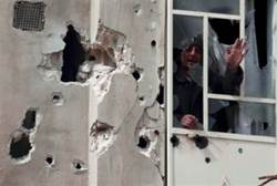 A man shouts from window after shelling by Assad's army