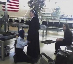 An elderly Catholic nun being frisked by a Muslim security agent.