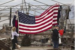 People raise the American flag among the wreckage of their homes devastated by Hurricane Sandy