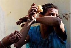 An injured protester who has been detained, eats with his hands bound