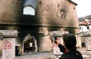 A young Muslim man takes a picture of his friend urinating on a burned down church in Kosovo.