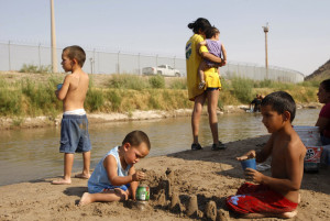 CHILDREN PLAY ALONG SHORES OF RIO GRANDE AT U.S. MEXICO BORDER