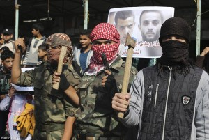 Masked Palestinians hold axes and a gun as they celebrate the massacre of four Jewish worshippers