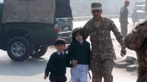 A soldier escorts schoolchildren from the Army Public School that is under attack by Taliban gunmen in Peshawar