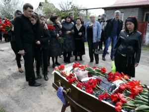Relatives of Donetsk deputy Volodymyr Rybak, mourn next to his coffin during a funeral in the village of Horlivka, in eastern Ukraine
